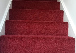 High quality red stair carpet showing the first four steps pointing up, installed by Garry Joy